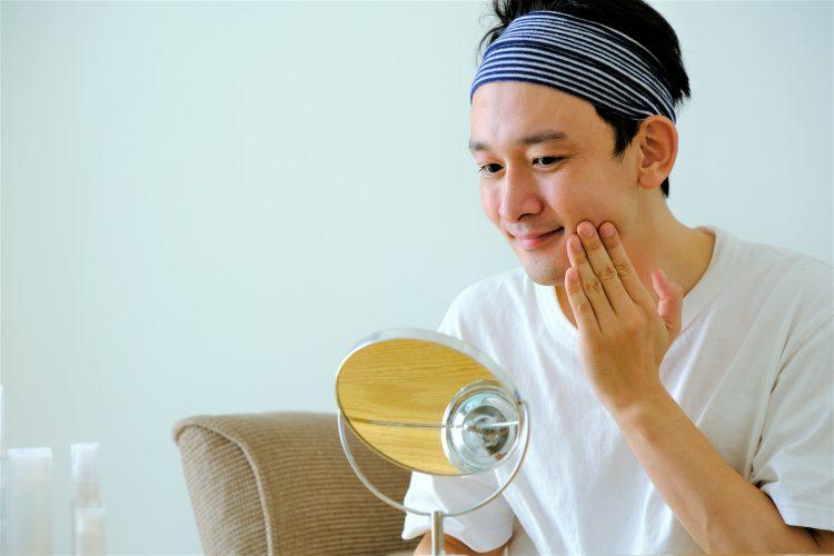 鏡で確認しながらメンズ化粧水を塗る男性