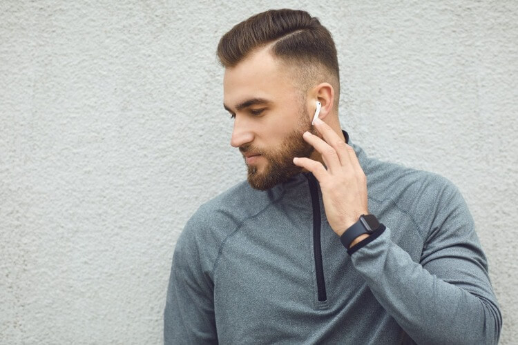 ワイヤレスイヤホンで音楽を聴く男性