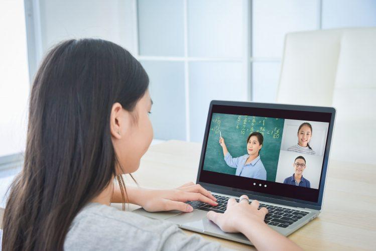 ノートパソコンのウェブカメラで通信する小学生
