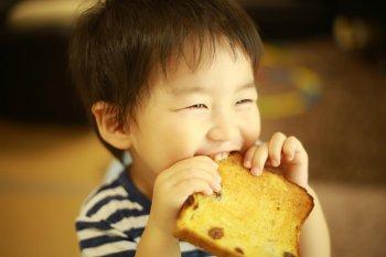 オーブンとトースターで焼いたパンを食べる子ども