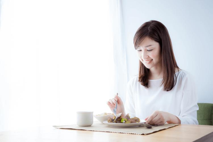 電気圧力鍋でつくった朝食を食べる女性