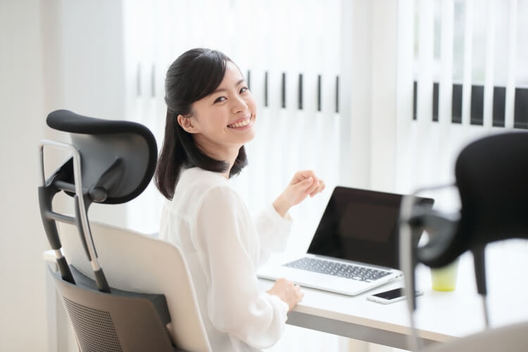 ワーキングチェアに座って仕事をする女性