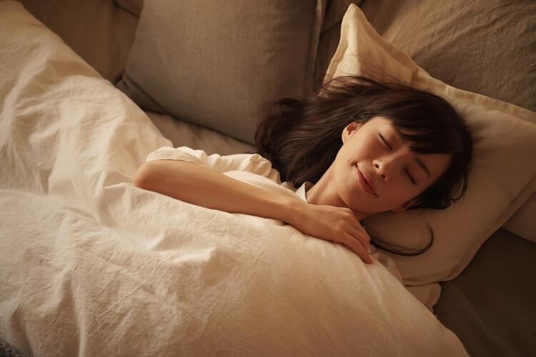 空気清浄機のかかった部屋で睡眠をとる女性