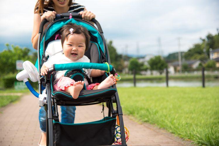 お母さんに押される赤ちゃんの乘ったベビーカー