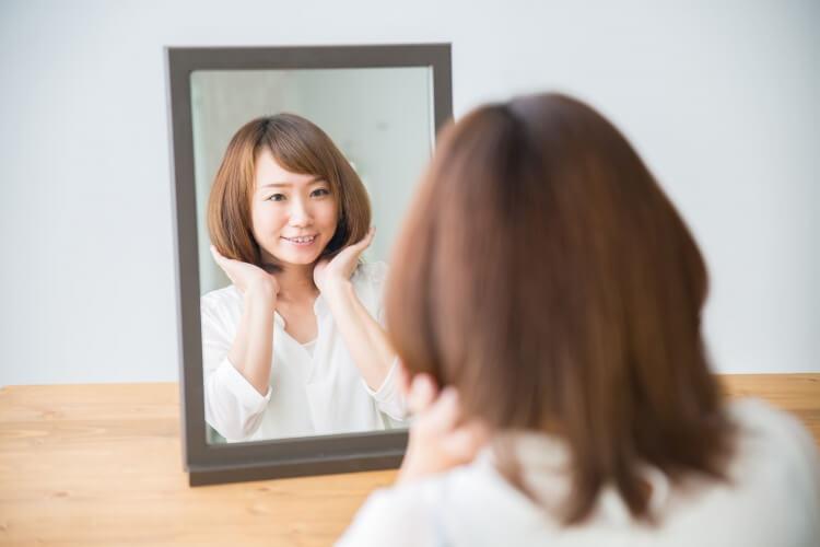 鏡で自分の髪を確認する女性