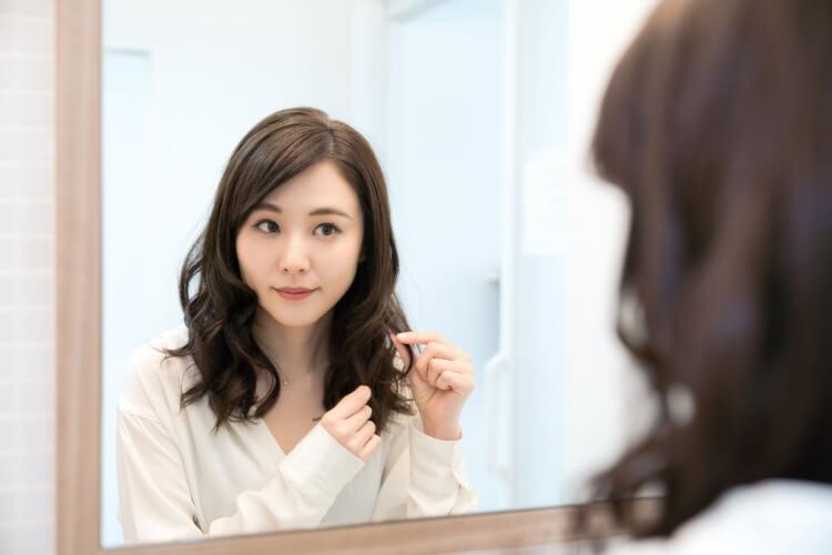 鏡の前で髪を触る女性