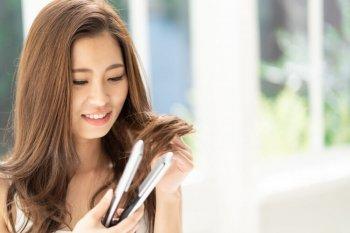コードレスヘアアイロンを使う女性