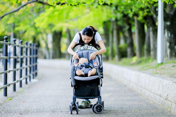 ベビーカーに乘った赤ちゃんをあやすお母さん