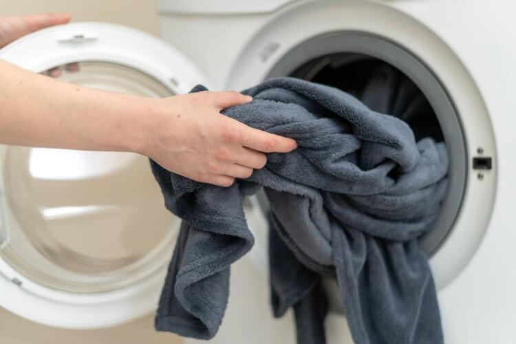 洗濯機から取り出される毛布