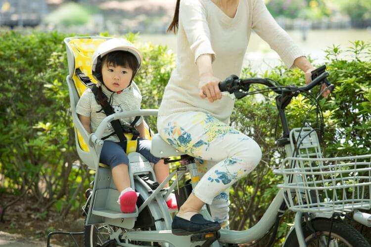 子ども用ヘルメットを着けて自転車の後部座席に乗る幼児