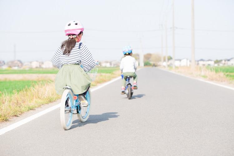 子ども用ヘルメットを着けて自転車に乗る男の子と女の子