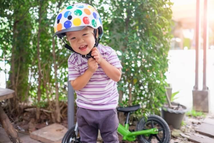 ヘルメットを外そうとする幼稚園児