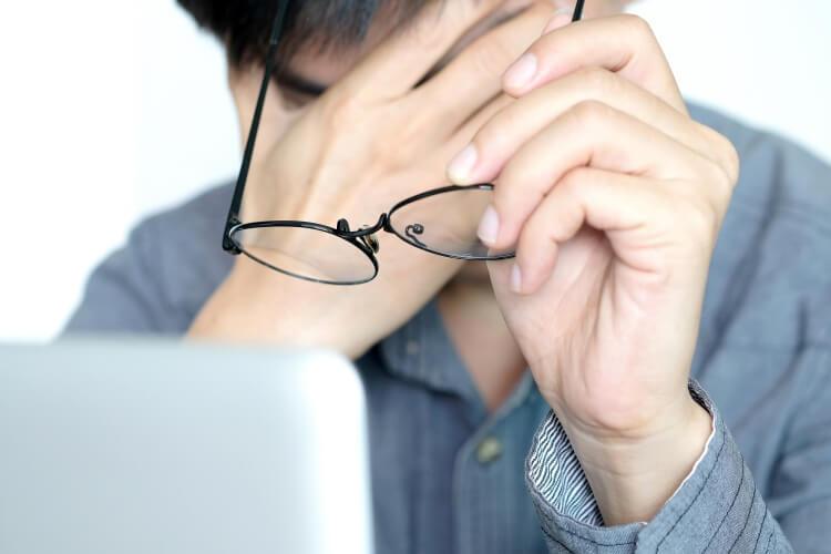 目が疲れて、メガネを外す男性
