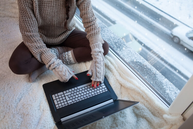 ハンドウォーマーを付けてパソコンを操作する女性