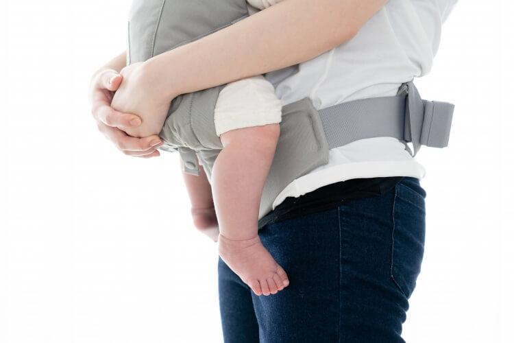 乳幼児をだっこ紐で抱えるお母さん