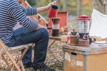 キャンプでコーヒーミルを使う男性