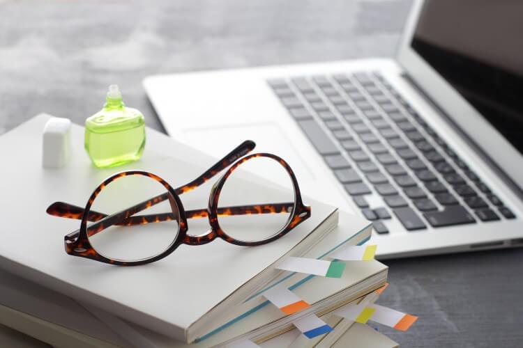 デスクの上に置かれたパソコンとメガネ