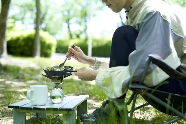 キャンプ中に食事をとる人