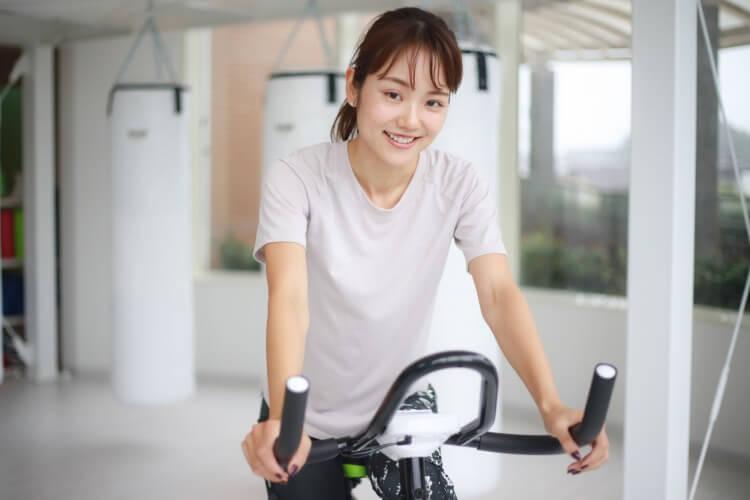 フィットネスバイクにまたがる女性