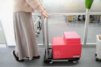 軽量な折り畳み台車で荷物を運ぶ女性