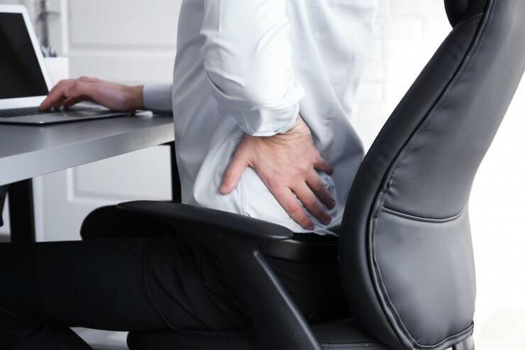 デスクワーク中の腰痛に悩む男性