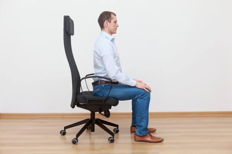 正しい姿勢でデスクチェアに座る男性