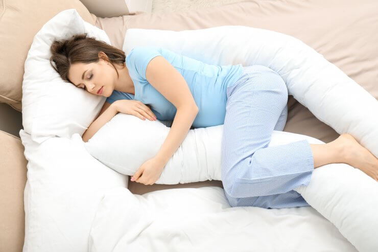 抱き枕を抱えて眠る妊婦