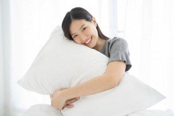 抱き枕を抱える女性のイメージ