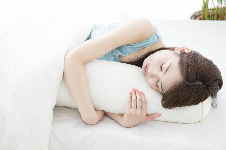 抱き枕を抱えて眠る産後ママのイメージ
