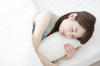 抱き枕を抱える女性