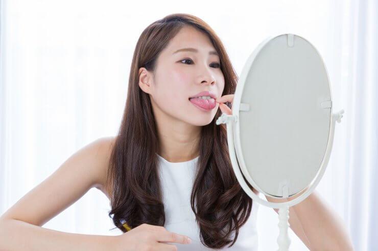 鏡で舌を見る女性