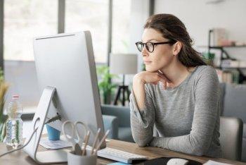 パソコンを使ってデスクワーク中、ブルーライトを浴びている女性